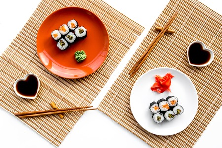 Sushi roll with salmon and avocado on plate with soy sauce, chopstick, wasabi on white background.