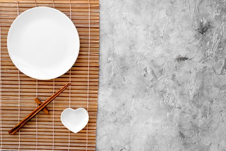 Table setting for sushi roll. Empty plate on mat near chopstick on grey table top view. Banco de Imagens