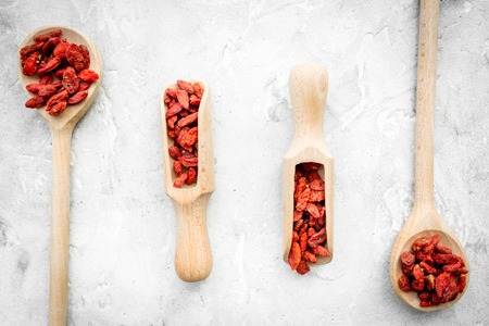 Wooden spoons with dried goji berries on grey background top view.