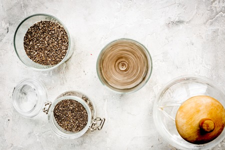 grained: Soak chia seeds in water. Grey background top view. Stock Photo