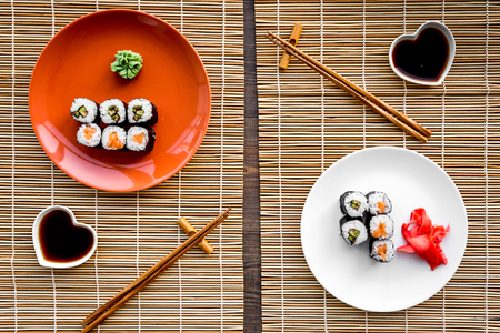 Sushi roll with salmon and avocado on plate with soy sauce, chopstick, wasabi on mat background.