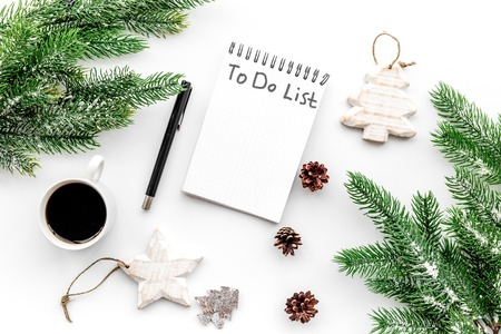 Make to do list for new year. Notebook among new year decorations on white background top view.