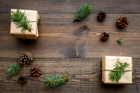 Gifts for new year wrapped in craft paper near spruce branches and cones on wooden background top view.