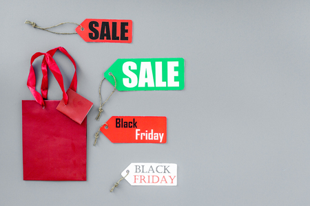 Sale and black friday labels near paper shopping bag on grey background top view.