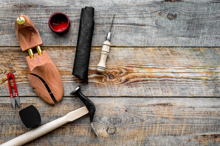 Shoe repair. Wooden last, hammer, awl, knife, thread on wooden background top view copyspace Stock Photo