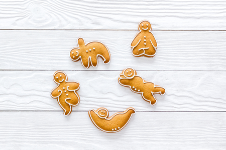 Gingerbread cookies in shape of yoga asanas on white wooden background top view