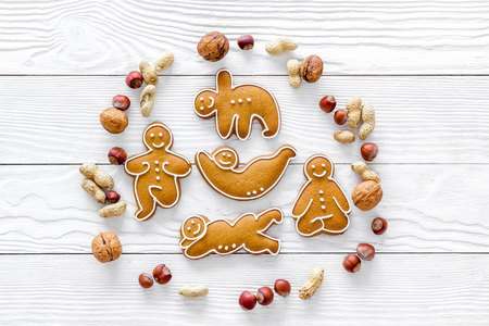 Healthy food for sportsman. Cookies in shape of yoga asanas near nuts on white wooden background top view copyspace Reklamní fotografie
