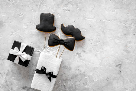 Birthday gift for men. Wrapped box, cookies in shape of black tie, mustache, hat. Grey background top view copyspace Stock Photo