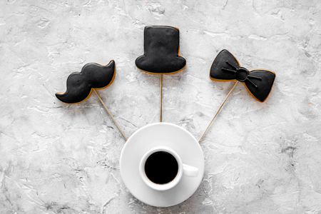 Men birthday concept. Cookies in shape of black tie, mustache, hat. Grey stone background top view
