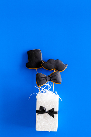 Happy Fathers day cards. Black tie, mustache and hat cookies in gift. Blue background top view copyspace Stock Photo