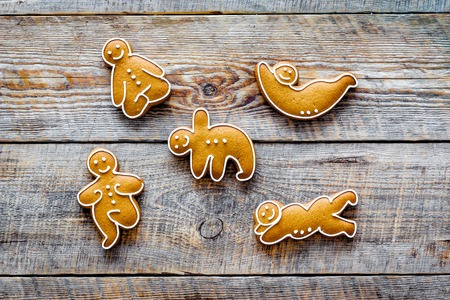 Gingerbread cookies in shape of yoga asanas on wooden background top view