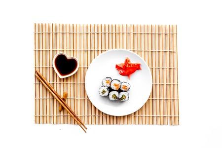 스시 롤 연어와 아보카도 간장, 젓가락,와 사비와 함께 접시에 롤. 흰색 배경 상위 뷰