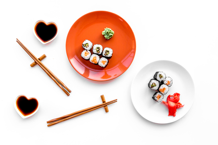 Sushi roll with salmon and avocado on plate with soy sauce, chopstick, wasabi on white background top view Stock Photo