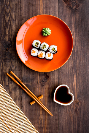 Sushi roll with salmon and avocado on plate with soy sauce, chopstick, wasabi on wooden table background top view