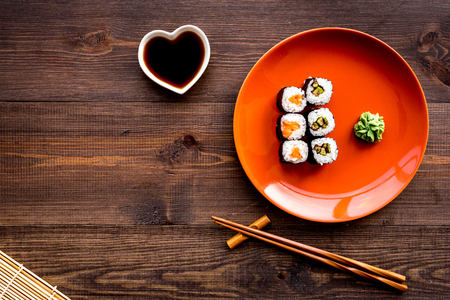 Sushi roll with salmon and avocado on plate with soy sauce, chopstick, wasabi on wooden table background top view copyspace