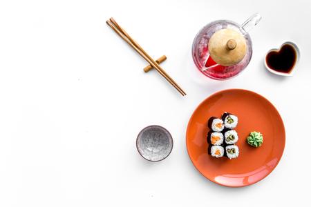 간장, 젓가락, 흰색 배경에와 사비와 함께 접시에 연어와 아보카도 스시 롤 상위보기 copyspace