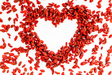 Dried goji berries in heart shape on white background top view copyspace pattern