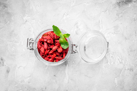 Dried goji berries in glass jar on grey background top view copyspace Stock Photo
