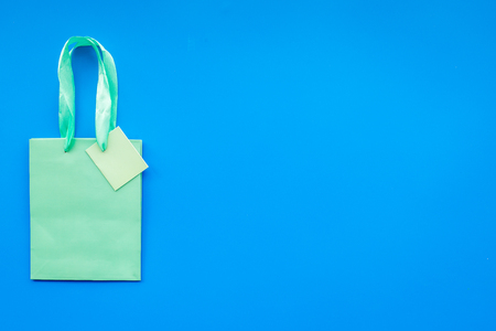 Turquoise bright shopping bag on blue background top view copyspace Stock Photo