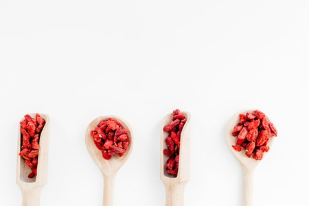 Wooden spoons with dried goji berries on white background top view copyspace 版權商用圖片