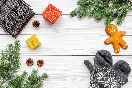 Cozy christmas evening. Cookies, spruce branch, knitten mittens on white wooden background top view copyspace Stock fotó