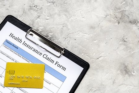 Buy health insurance. Document, pad, pen and bank card on grey background top view copyspace