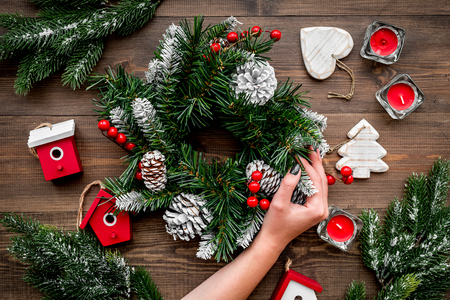 Christmas decorations. Wreath and toys on wooden background top view