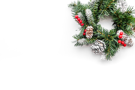 Christmas wreath woven of spruce branches with red berries on white background top view copyspace