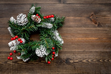 Christmas wreath woven of spruce branches with red berries on wooden background top view copyspace