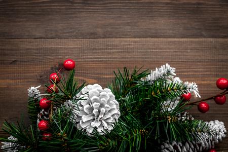 Weihnachtskranz gesponnen von den Fichtenzweigen mit roten Beeren auf Draufsichtspottbild des hölzernen Hintergrundes Standard-Bild - 88852271
