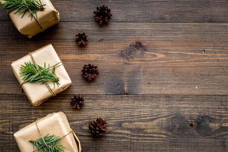 Gifts for new year wrapped in craft paper near spruce branches and cones on wooden background top view pattern copyspace Stock Photo