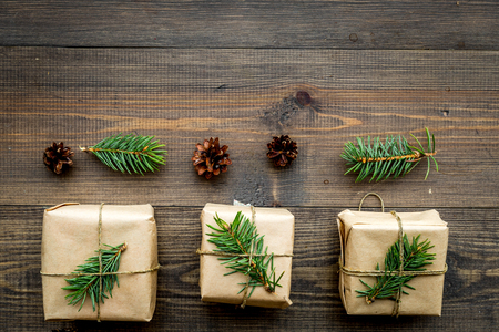 Gifts for new year wrapped in craft paper near spruce branches and cones on wooden background top view pattern copyspace Stock fotó
