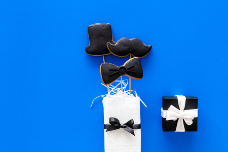 Happy Fathers day cards. Black tie, mustache and hat cookies and gift. Blue background top view copyspace