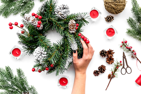 Make christmas wreath. Hand hold spruce branches, cones, threads, sciccors on white background top view