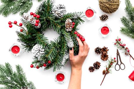 Weihnachtskranz machen. Übergeben Sie Grifffichtenzweige, Kegel, Threads, sciccors auf Draufsicht des weißen Hintergrundes Standard-Bild - 88852414