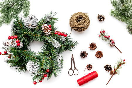 Make christmas wreath. Spruce branches, cones, threads, sciccors on white background top view