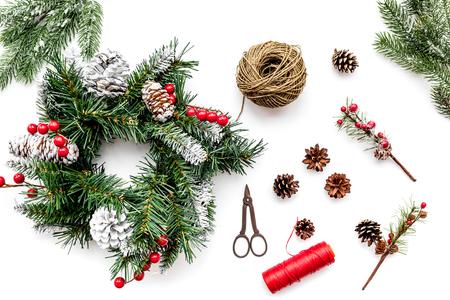 Weihnachtskranz machen. Fichtenzweige, Kegel, Threads, Sciccors auf Draufsicht des weißen Hintergrundes Standard-Bild - 88852420