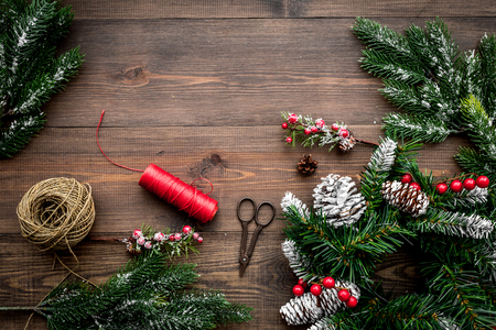 Make christmas wreath. Spruce branches, cones, threads, sciccors on wooden background top view copyspace Reklamní fotografie