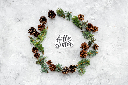 Hello Winter hand lettering. Winter pattern with spruce branch and cones on grey background top view copyspace Stock fotó