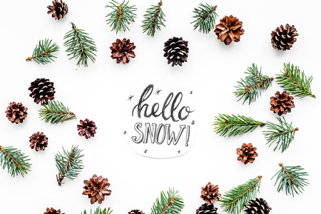 Hello snow hand lettering. Winter pattern with spruce branch and cones on white background top view Stock fotó