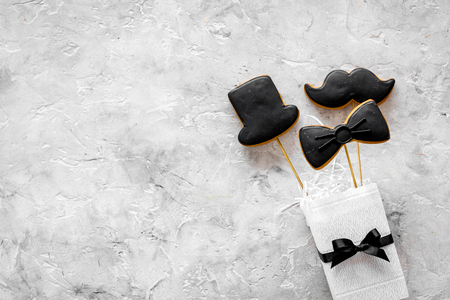 Men birthday concept. Set of cookies in shape of black tie, mustache and hat. Grey stone background top view copyspace