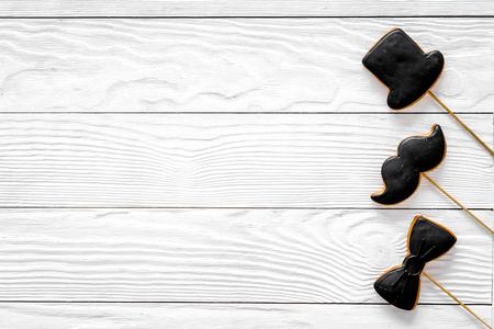 Mannen verjaardag concept. Set van cookies in de vorm van een zwarte stropdas, snor en hoed. Witte houten hoogste mening als achtergrond copyspace Stockfoto