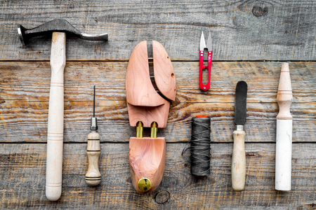 Shoe repair. Wooden last, hammer, awl, knife, thread on wooden background top view Banco de Imagens