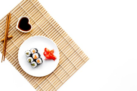 Sushi roll with salmon and avocado on plate with soy sauce, chopstick, wasabi on mat. White background Top view copyspace