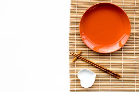 De instelling van de tabel voor sushi roll. Lege plaat op mat dichtbij eetstokje en kom voor sause op witte hoogste mening als achtergrond copyspace