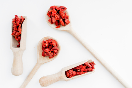 Wooden spoons with dried goji berries on white background top view copyspace Banco de Imagens