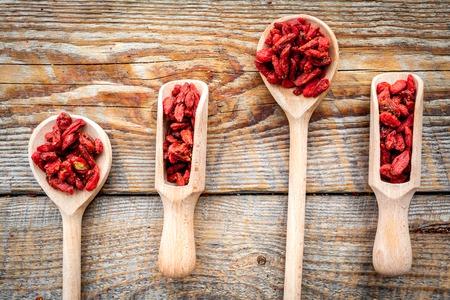 Wooden spoons with dried goji berries on wooden background top view Zdjęcie Seryjne