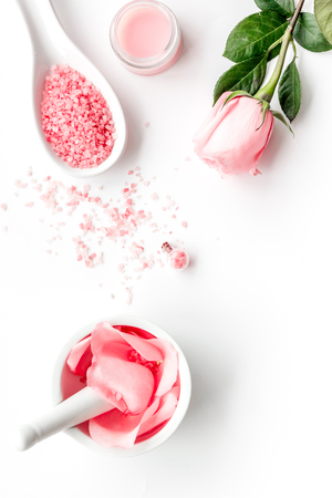Make cosmetics with rose  oil. Mortar with rose petals and pestle on white top view copyspace