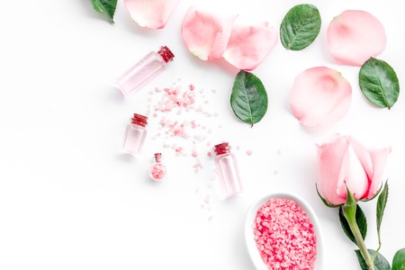 Pattern with rose oil cosmetics. Rose petals, spa salt on white top view copyspace