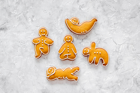 Gingerbread cookies in shape of yoga asanas on stone top view mock up